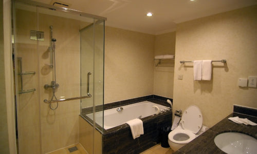 a clean modern bathroom with shower and bath, toilet and wash basin